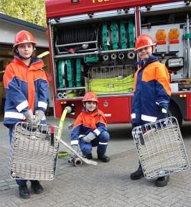 3 Kinder stehen mit der JF-spezifischen Ausrüstung vor dem LF10